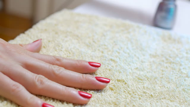 Woman applying red nail polish after manicure treatment