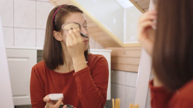 woman applying setting powder around her eyes with a brush - caucasian appearance stock videos & royalty-free footage