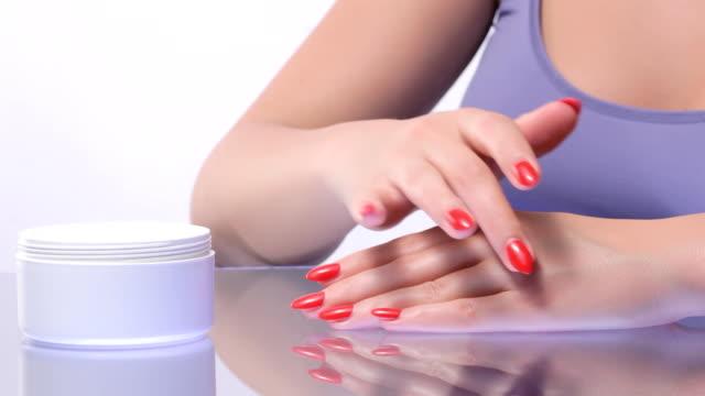 女性は、お肌の保湿剤で手します。 - マニキュア液点の映像素材/bロール