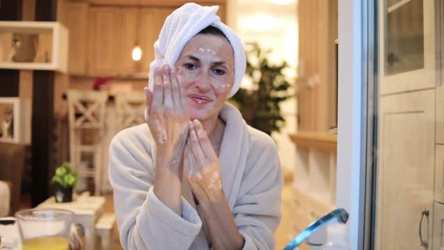kvinna som tillämpar hud fuktgivande grädde ont händer - en äldre kvinna med vitiligo gäller fuktighetskräm på händerna - applicera bildbanksvideor och videomaterial från bakom kulisserna