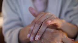 Woman applying skin moisturizing cream ont hands - An elderly woman with vitiligo applies moisturizer on her hands