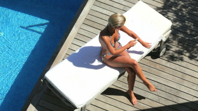 WS HA Woman applying sun cream and sunbathing on poolside / Andratx, Mallorca, Spain