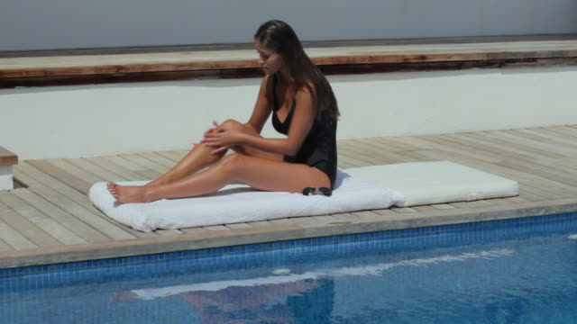 ws woman applying sun cream on poolside / andratx, mallorca, spain - swimming costume stock videos and b-roll footage