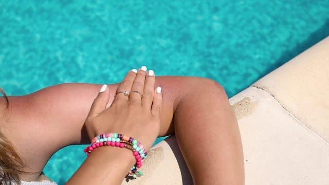 donna che applica lozione solare sul braccio con in piscina in una giornata calda e soleggiata. - sunbathing video stock e b–roll