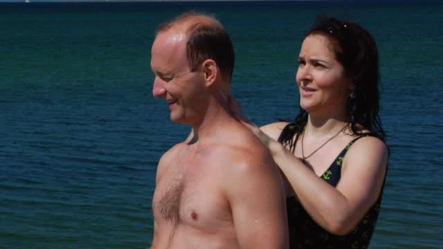 CU, Woman applying sunscreen on man's back on beach, North Truro, Massachusetts, USA