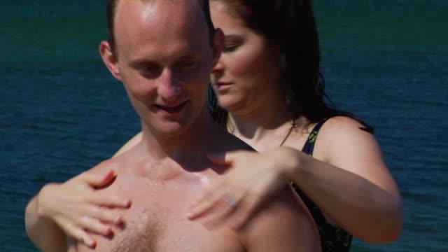 CU, TU, Woman applying sunscreen on man's back on beach, North Truro, Massachusetts, USA