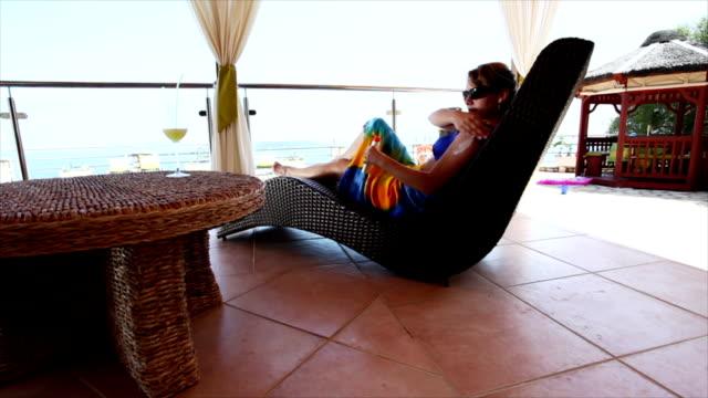donna applicando suntain solare presso la piscina - balcone video stock e b–roll