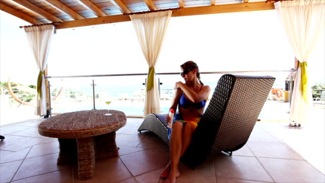 Woman applying suntain lotion by the pool