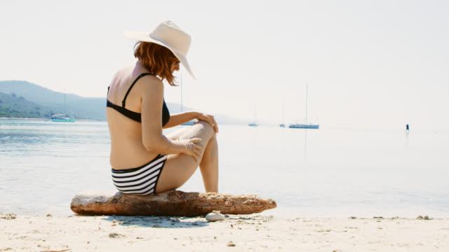WS Woman applying suntan lotion on the beach