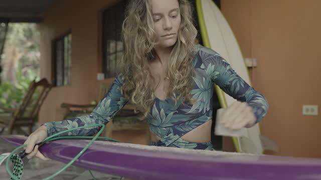 vídeos y material grabado en eventos de stock de woman applying wax to surfboard / el tunco, la libertad, el salvador - enfoque diferencial