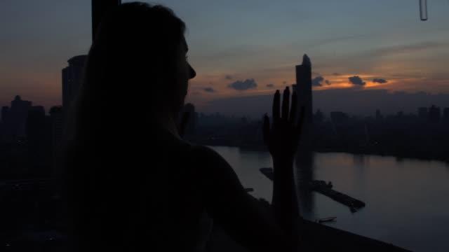 donna apprezzando una vista meravigliosa da una stanza di bangkok - guardare fuori dalla finestra video stock e b–roll