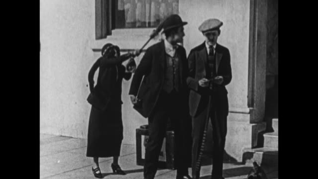1924 woman approaches fighting men, hits one with umbrella and makes him leave - fight stock videos & royalty-free footage