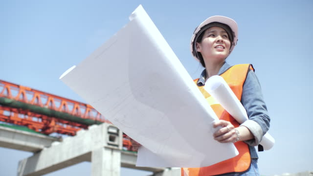 woman architect discussing on blueprint at construction site - architetto video stock e b–roll