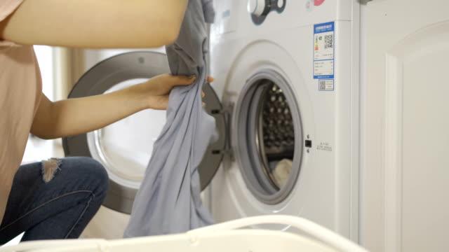 女性は洗濯機を使っている - 洗濯かご点の映像素材/bロール