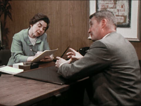 vídeos de stock, filmes e b-roll de 1969 woman arguing with man at his desk / woman standing up and intimidating man - agressão