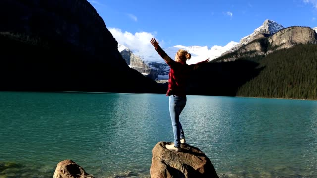 Woman arms outstretched by beautiful lake