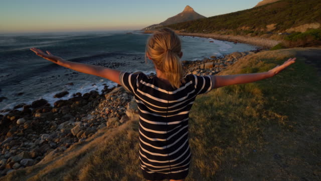 Woman arms outstretched by the coast