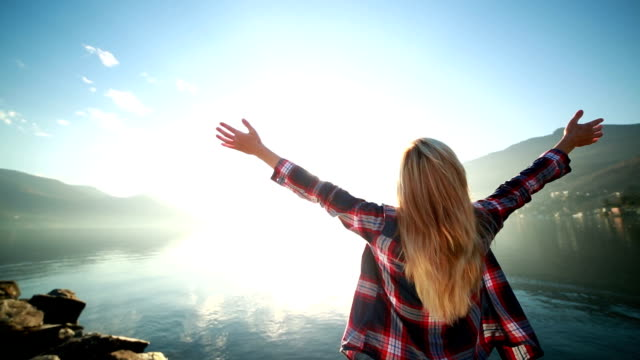 Woman arms outstretched by the lake