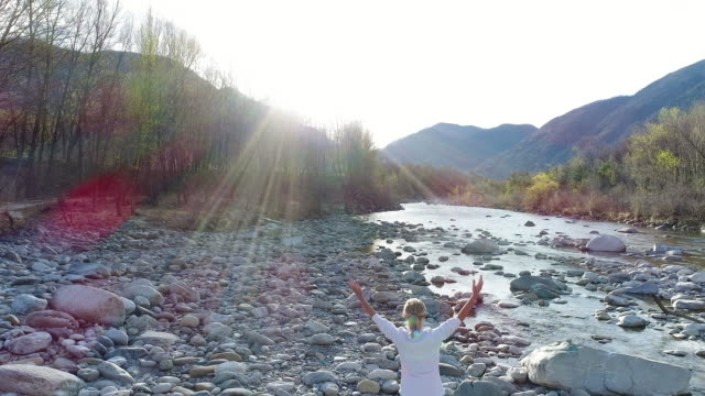 woman arms outstretched by the river