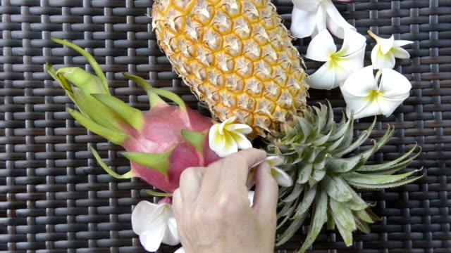 Woman arrange Frangipani flowers, Pineapple and Dragon fruit, Pitaya (Hylocereus undatus)