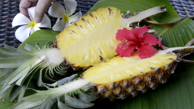 Woman arrange Hibiscus and Frangipani flowers at sliced Pineapple