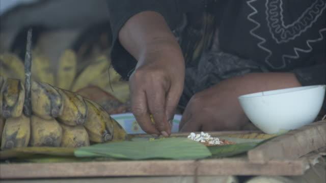 vidéos et rushes de a woman arranges rice on a leaf. - châle