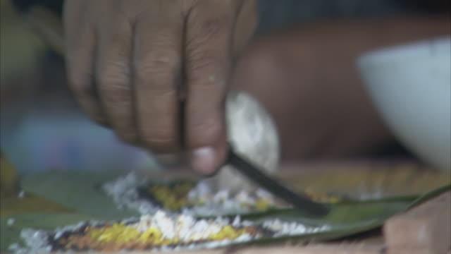 vidéos et rushes de a woman arranges rice on a leaf with a knife. - châle