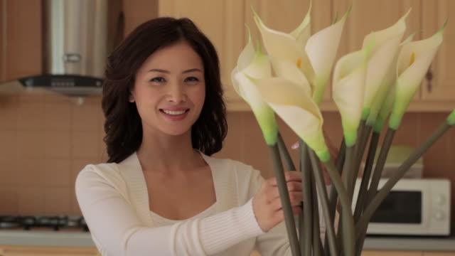 ms woman arranging calla lilies in kitchen / china - オランダカイウユリ点の映像素材/bロール