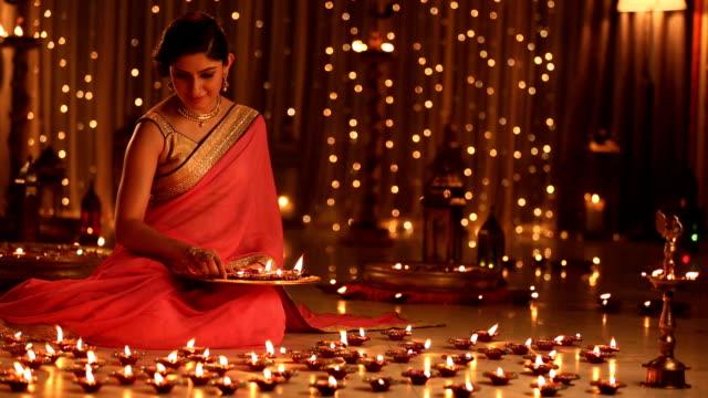 ms woman arranging diya on floor during diwali festival - 盆点の映像素材/bロール