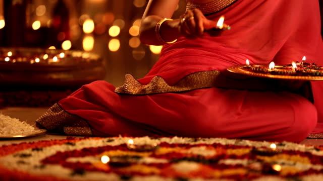 CU Woman arranging diyas on flower rangoli during diwali festival