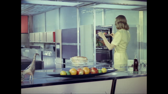 MS Woman arranging food in refrigerator in futuristic kitchen / United States