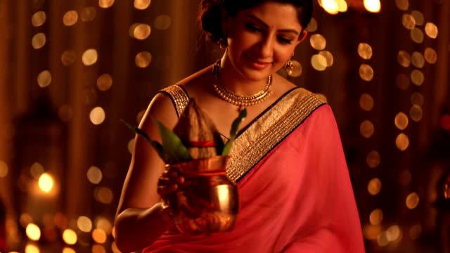 MS TD Woman arranging kalash on flower rangoli during diwali festival