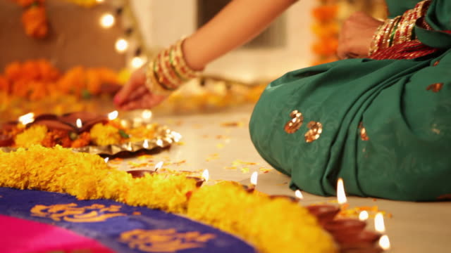 Woman arranging oil lamp in diwali festival