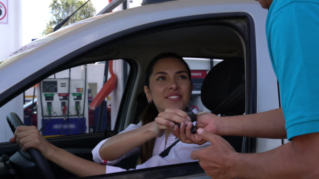 Woman arriving at a gas station to fuel her car