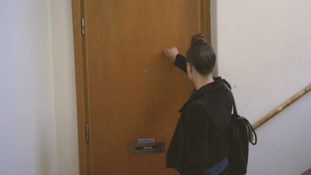 woman arriving at colleague's apartment - doorway stock videos & royalty-free footage