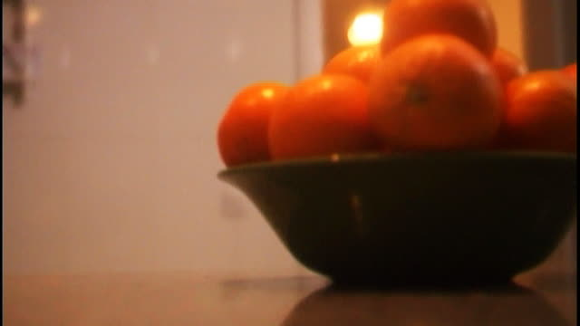 woman arriving home from work, putting coat on table by large bowl of oranges. - bowl stock videos and b-roll footage