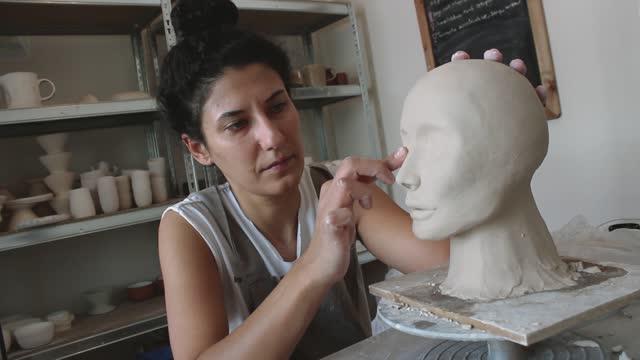 künstlerin arbeitet in ihrem atelier und macht skulptur - sculpture stock-videos und b-roll-filmmaterial