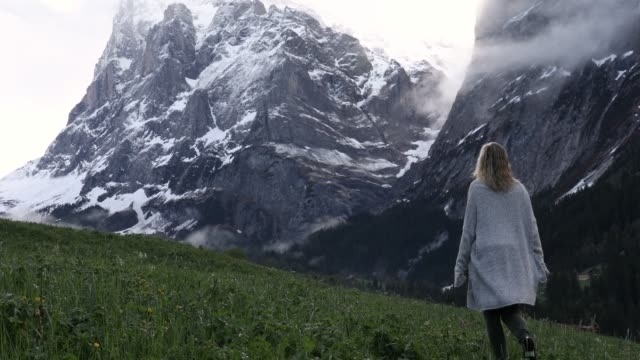 woman ascends meadow beneath towering snowy peaks - cardigan sweater stock videos & royalty-free footage