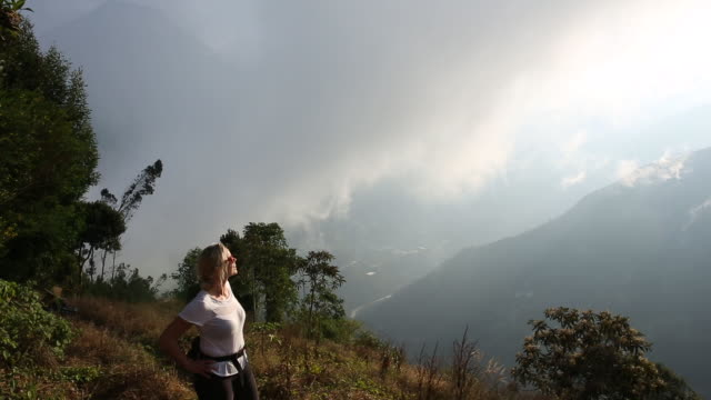 stockvideo's en b-roll-footage met woman ascends mountain path, above valley as mist rolls in - handen op de heupen