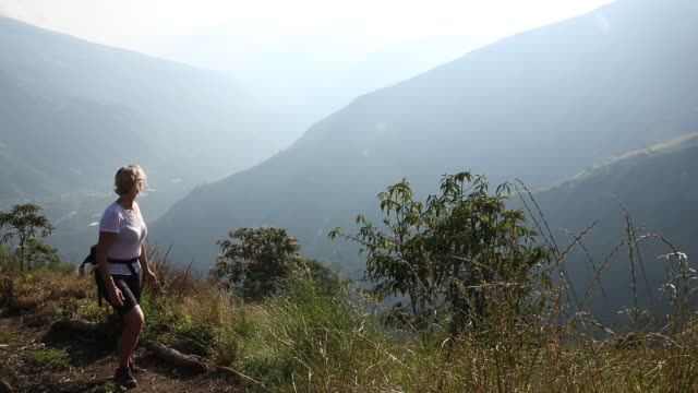 woman ascends mountain path, above valley - pedal pushers stock videos & royalty-free footage