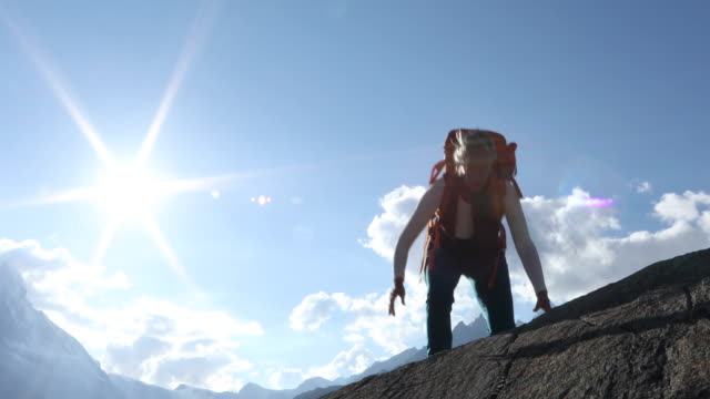 woman ascends rock cliff above valley, at sunrise - rucksack stock-videos und b-roll-filmmaterial