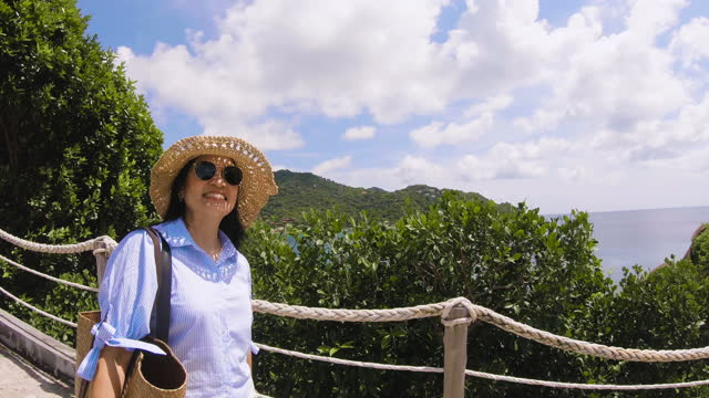 woman asia passenger enjoying the walk and exploring resort hotel and wearing a casual cloth with the sea and tropical green tree view - tropical tree stock videos & royalty-free footage