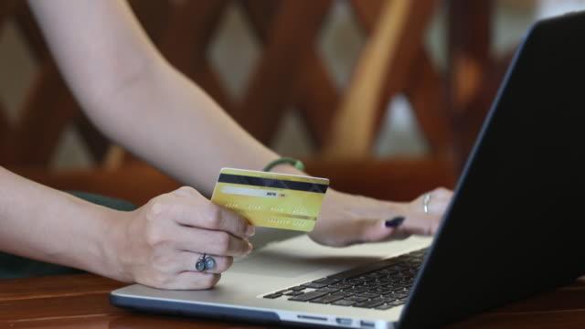 vidéos et rushes de femme asiatique en utilisant le téléphone et les achats de carte de crédit en ligne - credit card