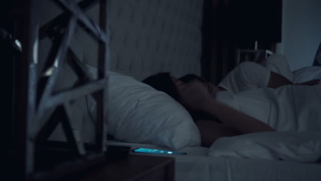 woman asleep in bed woken by alarm on mobile phone - ora di andare a letto video stock e b–roll