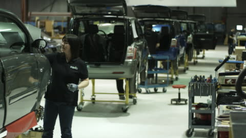 ws woman assembling electric car on production line, st. jerome, quebec, canada - in a row stock videos & royalty-free footage