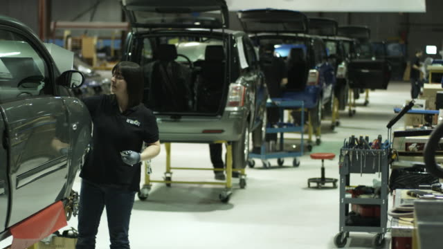stockvideo's en b-roll-footage met ws woman assembling electric car on production line, st. jerome, quebec, canada - autofabriek