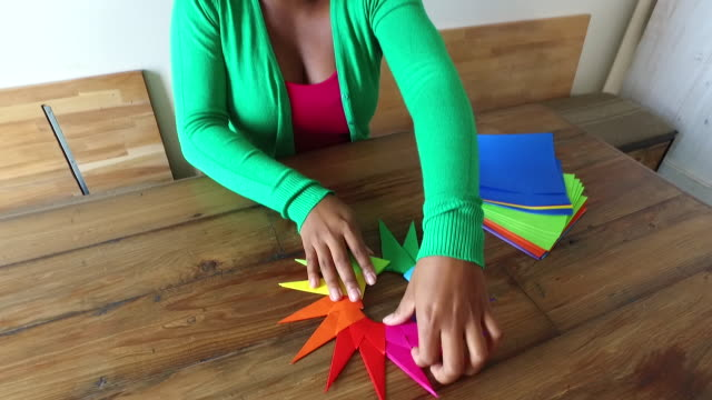 woman assembling origami in loft space - folding paper stock videos and b-roll footage
