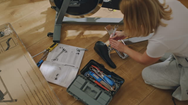 ms woman assembling the exercise bike she purchased online - exercise room stock videos & royalty-free footage