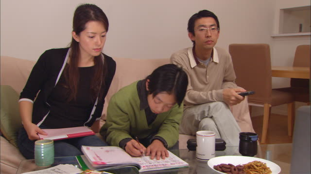 MS, Woman assisting son (10-11) doing homework, father watching television