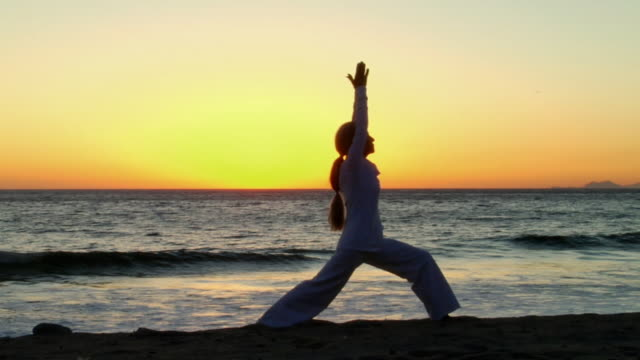 ws woman assuming warrior 2, triangle, and sun salutation yoga positions on beach at sunset/ sycamore cove, california - sun salutation stock videos & royalty-free footage